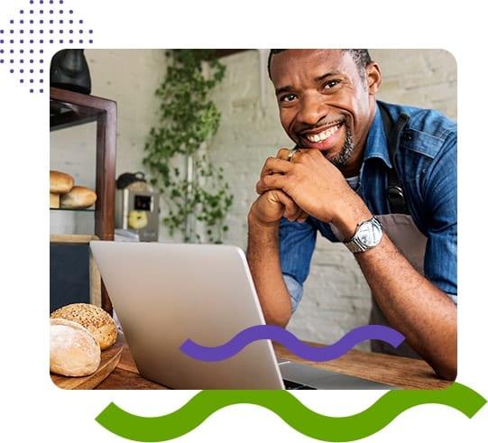 Imagem mostra empreendedor jovem e negro (dono de uma panificadora) trabalhando em frente ao computador, sorrindo.